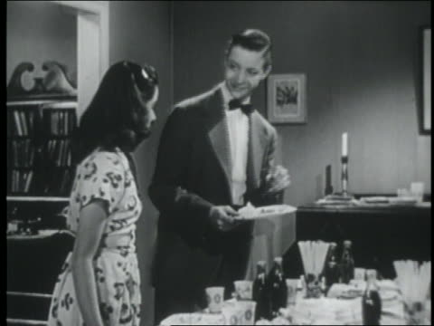 vídeos de stock e filmes b-roll de b/w 1946 teenage couple gets plates of food at refreshment table at party / sit down + talk - sentar se