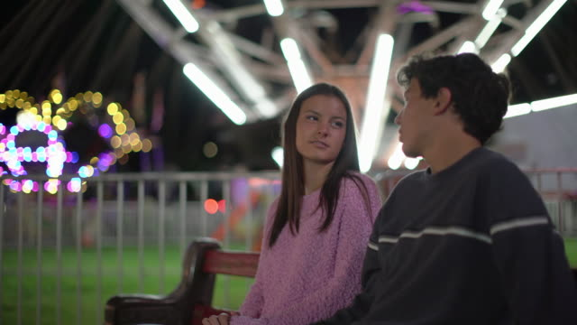 vidéos et rushes de ms teenage couple having fun at a carnival at night - couple d'adolescents