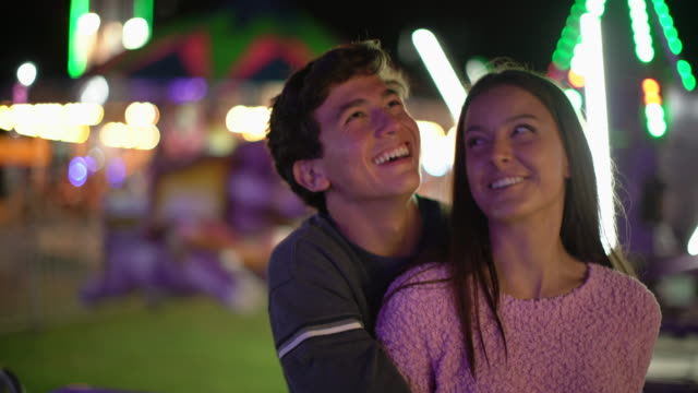 vidéos et rushes de cu teenage couple hugging at a carnival at night - couple d'adolescents