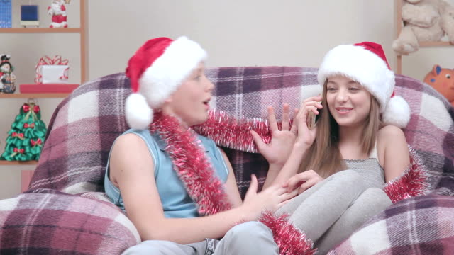 Teenage couple in Santa Claus hats talking on smartphone, smiling