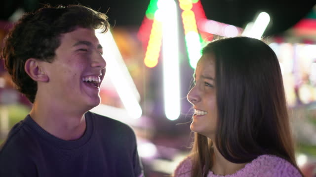 cu teenage couple laughing together at a fun fair - vergnügungspark stock-videos und b-roll-filmmaterial