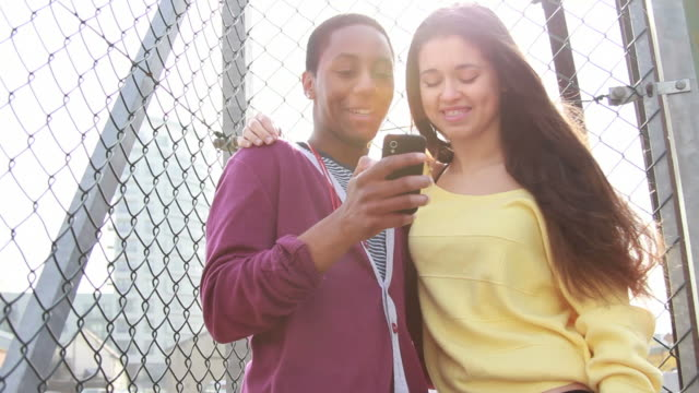 Teenage couple looking at mobile phone
