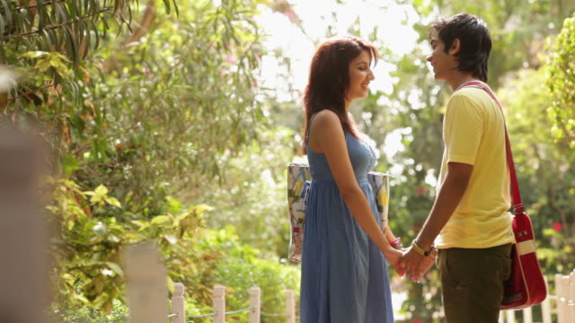 vidéos et rushes de teenage couple romancing in a garden  - couple d'adolescents