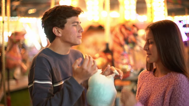 vidéos et rushes de ms teenage couple sharing cotton candy at a carnival at night - couple d'adolescents
