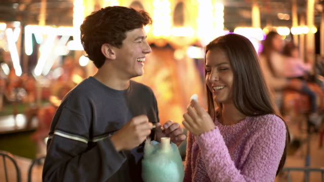 ms teenage couple sharing cotton candy at a carnival at night - teenage couple stock videos & royalty-free footage