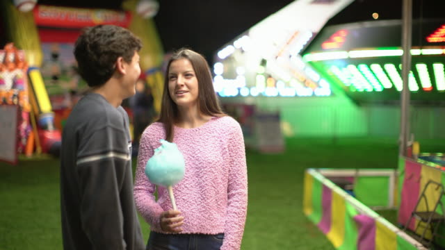 ws teenage couple sharing cotton candy at a carnival at night - teenage couple stock videos & royalty-free footage