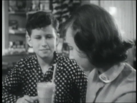 b/w 1955 teenage couple sharing milk shake at soda fountain - straw stock videos & royalty-free footage