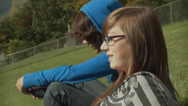 vidéos et rushes de cu teenage couple (14-15) sitting on grass and talking, cazenovia, new york, usa - couple d'adolescents