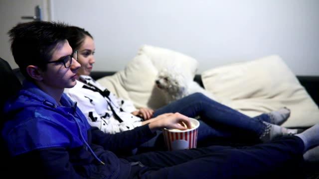 vídeos de stock, filmes e b-roll de casal adolescente sentado no sofá assistindo tv - new