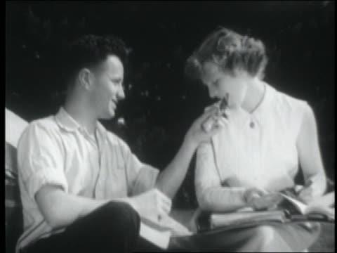 B/W 1955 teenage couple sitting outdoors sharing candy bar
