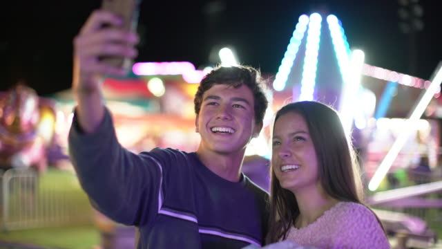 vidéos et rushes de ms teenage couple taking a selfie at night - couple d'adolescents