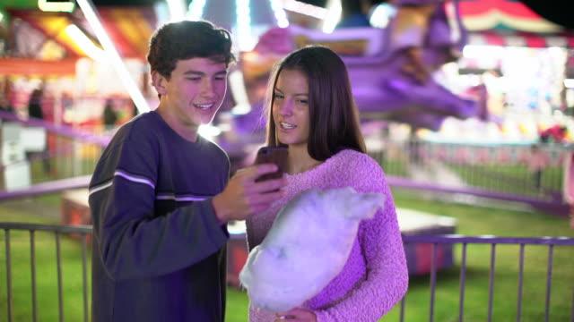 ms teenage couple texting at a carnival at night - 遊園地点の映像素材/bロール