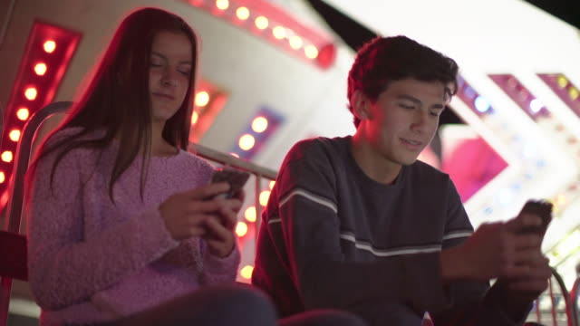 stockvideo's en b-roll-footage met ms teenage couple texting at night - tienerjongens