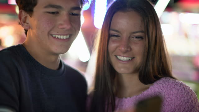 cu teenage couple texting on a phone at night - teenage couple stock videos & royalty-free footage