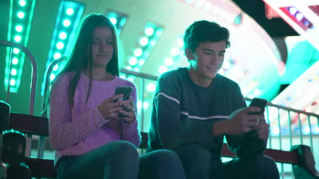 vidéos et rushes de ws teenage couple texting on their phones at night - petite amie