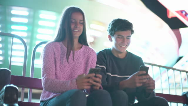 stockvideo's en b-roll-footage met ws teenage couple texting on their smart phones - handheld