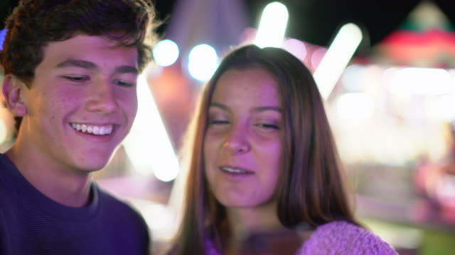vidéos et rushes de cu teenage couple using phone at a carnival at night - couple d'adolescents