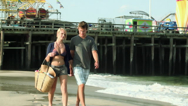 vidéos et rushes de teenage couple walking hand in hand on beach - 16 17 ans