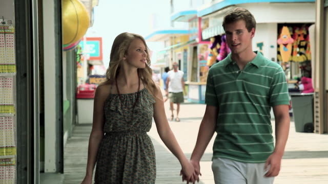 Teenage couple walking hand in hand on pier