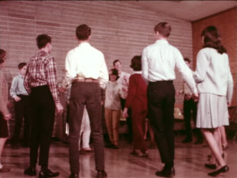 1965 teenage couples dancing in gym at YMCA youth dance / Indianapolis, Indiana / educational