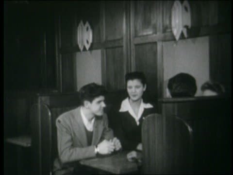 vidéos et rushes de b/w 1946 2 teenage couples getting up from booth at malt shop - couple d'adolescents