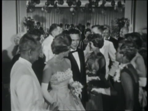 B/W 1961 teenage couples saying goodbye to chaperones at end of prom / Coca-Cola educational