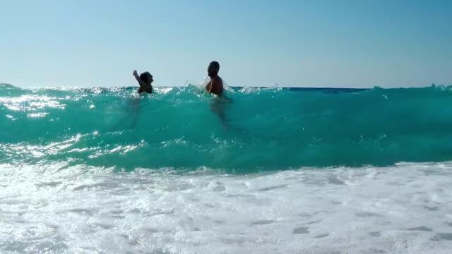 Teenager-Tochter mit seinem Vater viel Spaß in unglaublich blaue Meer, große Wellen Spaß