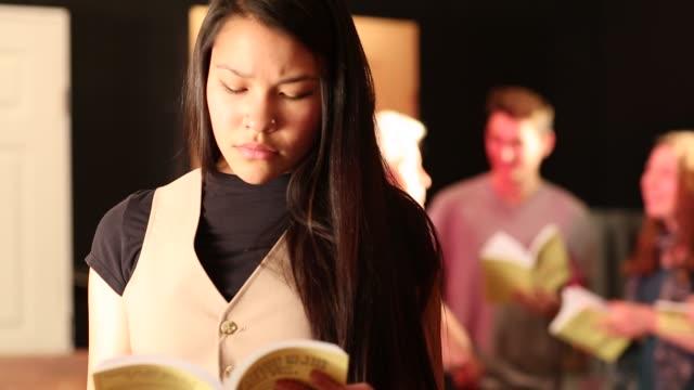 vídeos y material grabado en eventos de stock de teenage  drama students reading scripts and listening to their drama teacher - sólo una adolescente