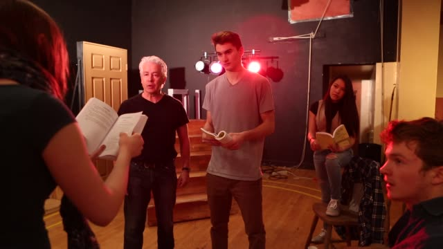 stockvideo's en b-roll-footage met teenage  drama students reading scripts and listening to their drama teacher - actrice