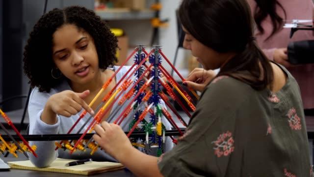 Teenage étudiants en génie placer finitions sur pont de modèle
