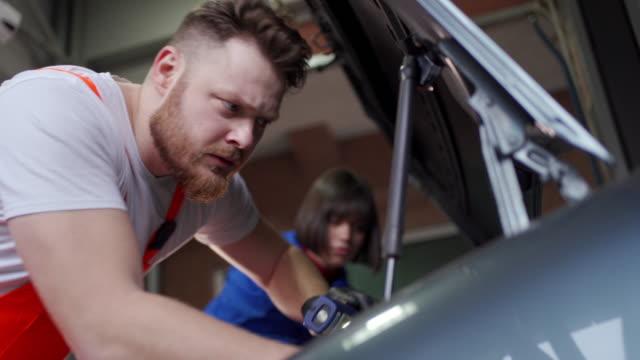 vídeos y material grabado en eventos de stock de mecánica adolescente y joven mecánico masculino reparando un coche en el taller de reparación de automóviles - waist up