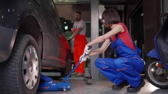 タイヤを膨らませる10代の女性整備士 - 空気弁点の映像素材/bロール