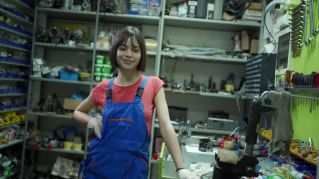 vidéos et rushes de mécanicien féminin d'adolescent souriant dans une salle de stockage - apprenti