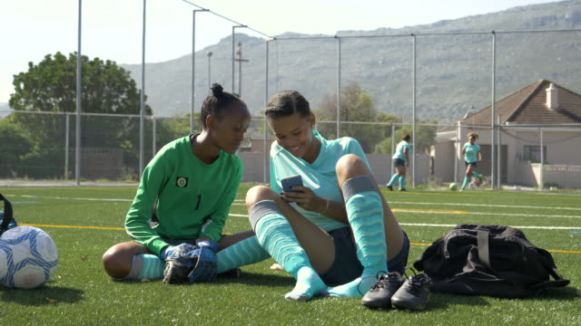 teenage female soccer players looking at phone - pitch stock videos & royalty-free footage