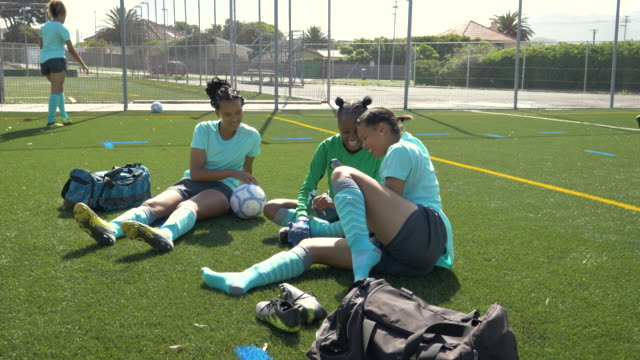vidéos et rushes de teenage female soccer players looking at phone - s'entraîner