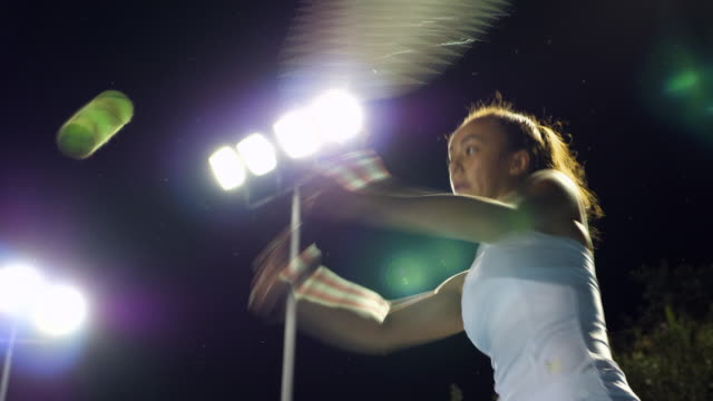 ms tu teenage female tennis player hitting return while practicing on outdoor court at night - teenage girls stock videos & royalty-free footage