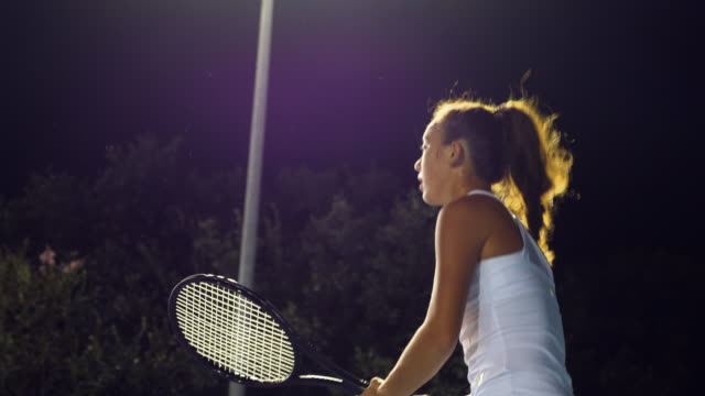 ms tu teenage female tennis player practicing backhand returns during workout on outdoor court at night - tennis racket stock videos & royalty-free footage