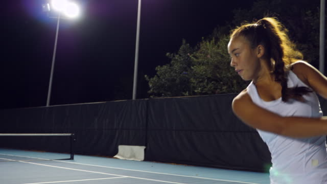 ms teenage female tennis player practicing on outdoor court at night - court stock videos & royalty-free footage
