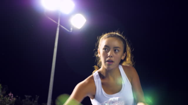 cu tu teenage female tennis player practicing returns at net on outdoor court at night - nur weibliche teenager stock-videos und b-roll-filmmaterial