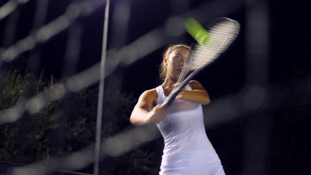 stockvideo's en b-roll-footage met cu tu teenage female tennis player practicing shots at net on outdoor court at night - atlete