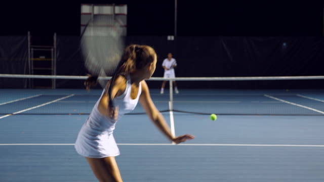 ms teenage female tennis player practicing with male teammate during workout on outdoor court at night - tennis stock videos & royalty-free footage