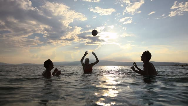 teenage friends enjoying their summer vacation, playing volleyball in the sea - teenager stock videos & royalty-free footage