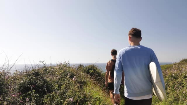 teenage friends walking along a coastal path down to the beach. - eco tourism stock videos & royalty-free footage