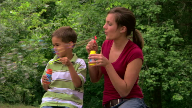 teenage girl and boy blowing bubbles - 子守り点の映像素材/bロール