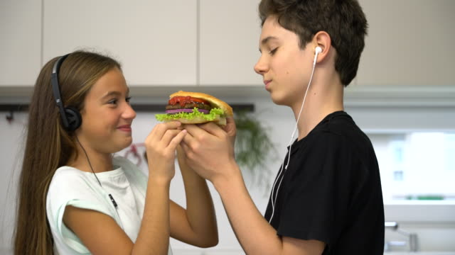 teenage girl and boy eating hamburgers together