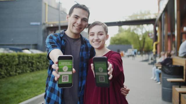 夏に屋外のスマートフォンでcovid-19ワクチンパスポートを持つ10代の少女と少年 - 見せる点の映像素材/bロール