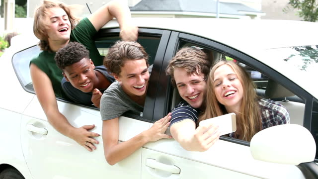 Teenage girl and four guys talking selfie from car