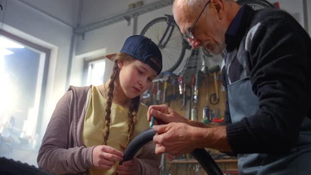stockvideo's en b-roll-footage met slo mo tiener meisje en haar grootvader herstellen van een band punctie in de werkplaats - piercen