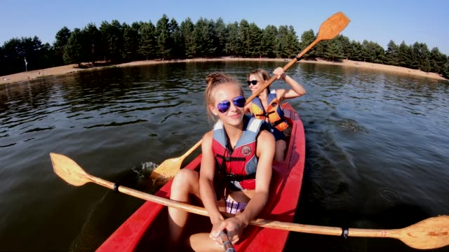 teenage girl and her mother are enjoying kayaking on lake - canoe stock videos & royalty-free footage