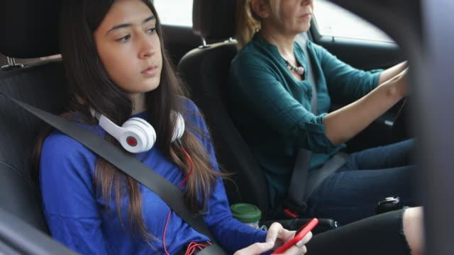 vidéos et rushes de adolescente et sa mère dans la voiture - casque audio